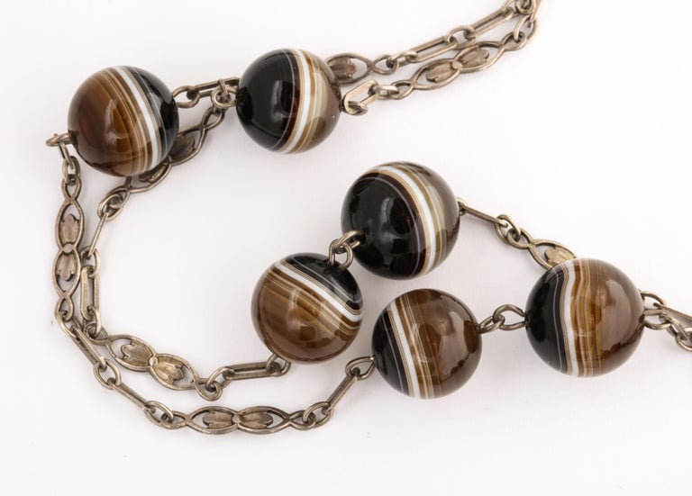Sturdy alternating links of rectangles and double tulips hold uniform banded agate beads. The distance between the agates vary sometimes kissing cousins sometimes three inches apart and other times five inches apart. The agate balls are brown, white
