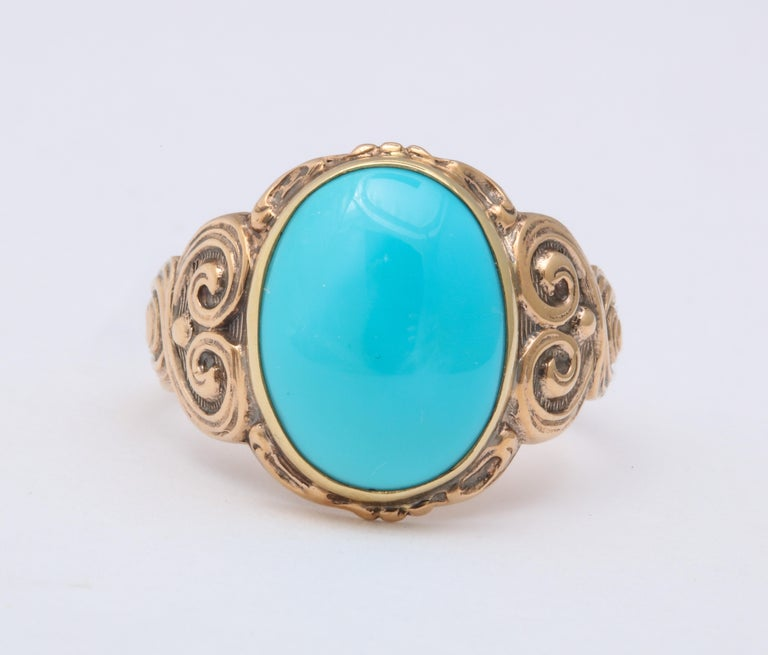 A 5.5 ct oval turquoise ring is cut in cabochon and set in a 14 kt engraved shank. The shank tapers from its repousse swirls on the shoulders. The ring is all original. The engraving travels half way around the finger. The collet keeps the turquoise