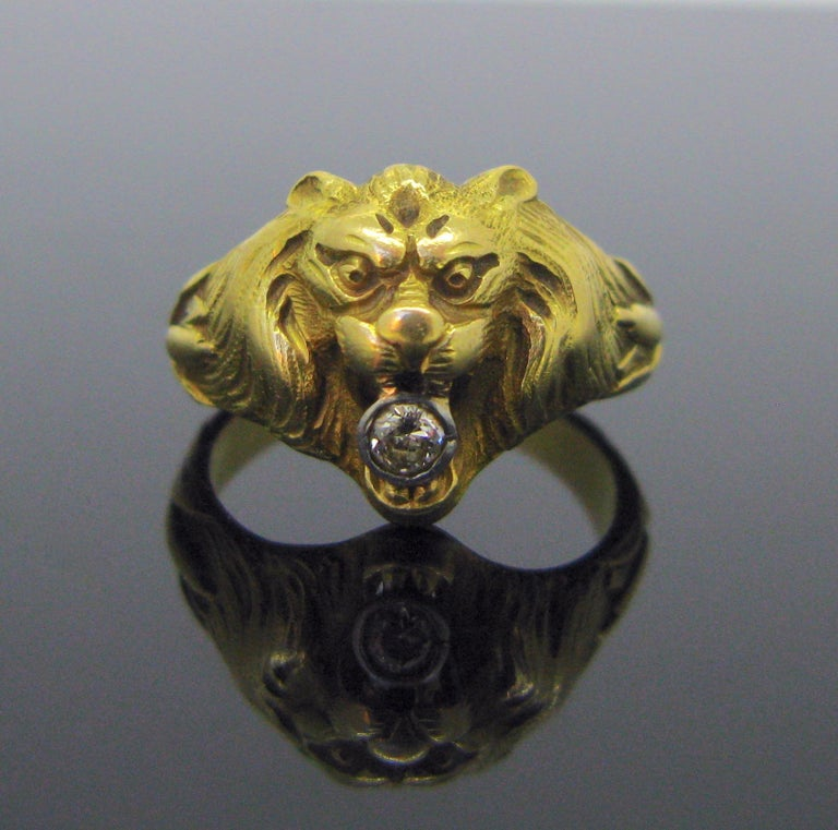 This ring was nicely designed into a Lion head. It has a strong design. It depicts a regal lion with flowing mane in exceptional detail. It holds in his jaws an old mine cut diamond weighing around 0.20ct. The ring is very good antique condition. It