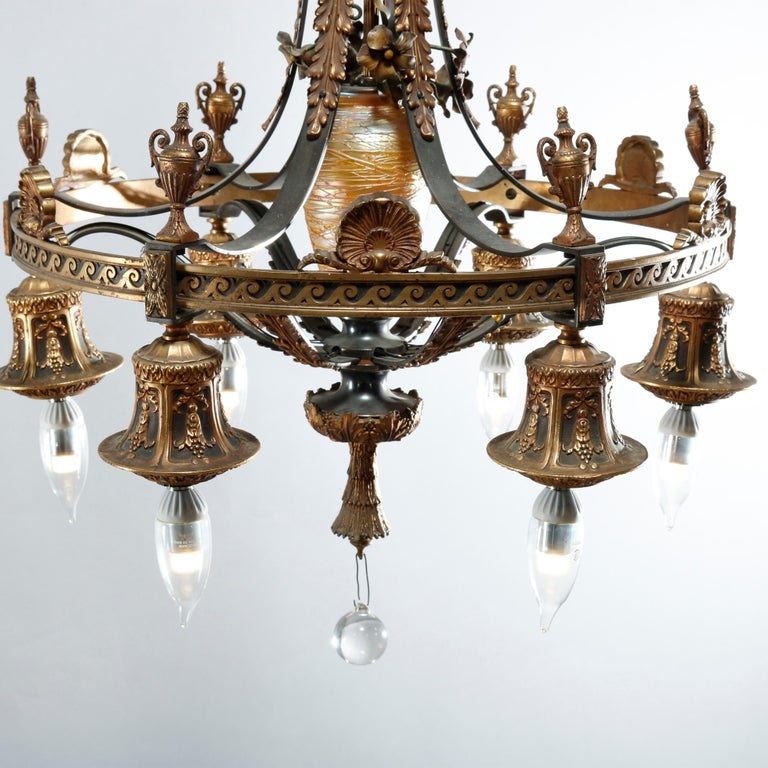 An antique Arts & Crafts chandelier offers gilt bronze frame having scroll, foliate and floral elements with six acanthus draped arms surrounding Quezal art glass font and terminating in drop lights with urn form finials, frame with stylized wave