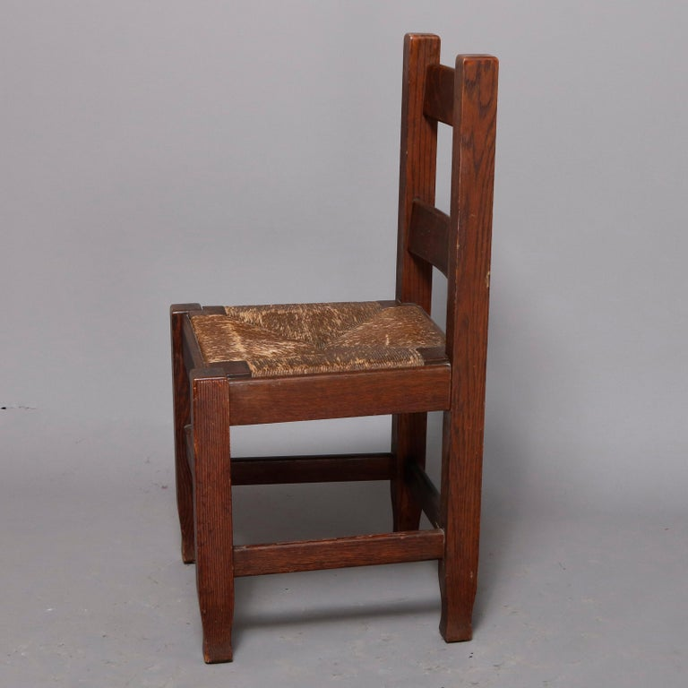 An antique Arts & Crafts mission oak desk chair by Joseph McHugh offers ladder back and rush seat and raised on straight and square legs terminating in slightly tapered feet, circa 1920  Measures - 36.25