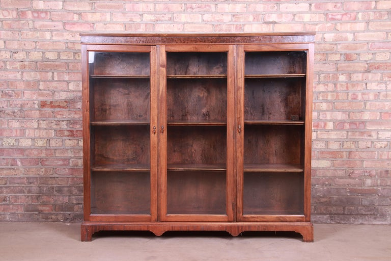A gorgeous antique Arts & Crafts glass front triple bookcase  USA, circa 1900  Mahogany with burled walnut trim, and original glass doors and brass hardware.  Measures: 59