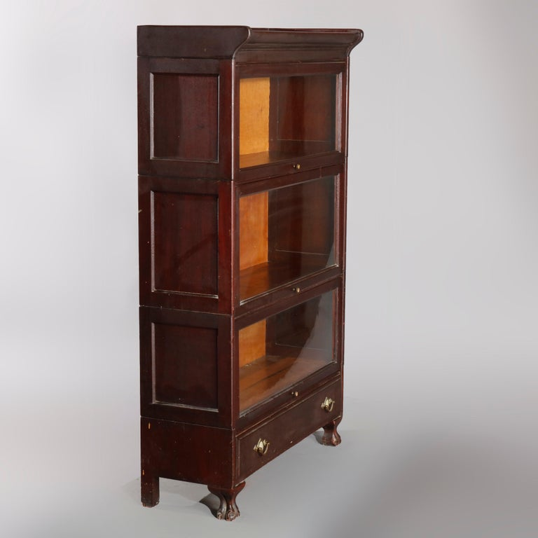 An Arts & Crafts sectional Barrister bookcase made in Grand Rapids offers mahogany construction with three stacks having a pull-down glass door on base with drawer having brass pulls with mother of pearl inlaid medallion and raised on cabriole legs
