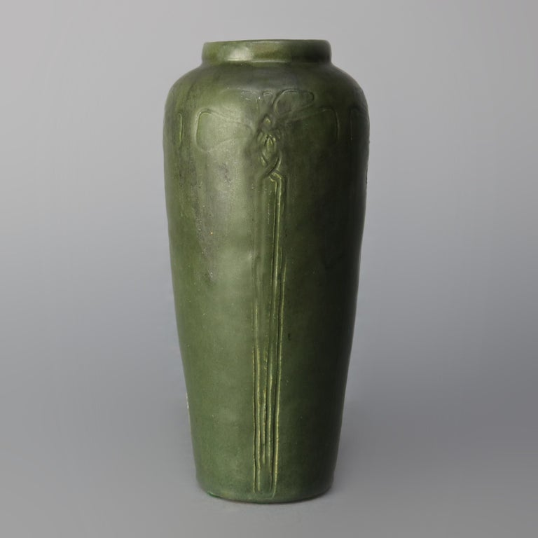 An antique Arts & Crafts art pottery vase in the manner of Grueby offers matte green glaze with repeating pattern of incised stylized flowers, artist signed CM, MC, WC, CW, EU or UE on base as photographed, elements of Marblehead and Walrath, circa