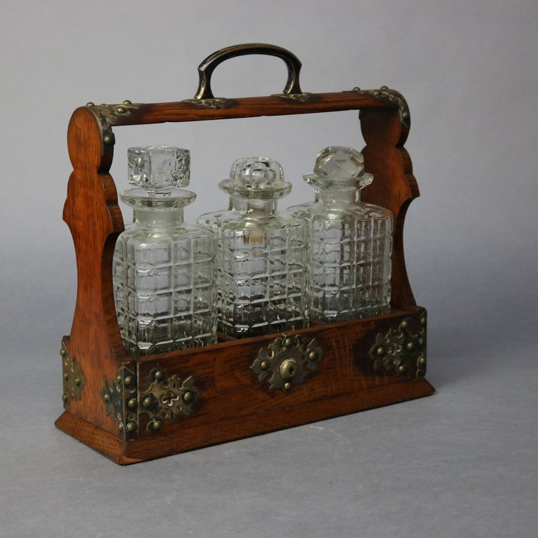 An antique Arts & Crafts Tantalus set offers shaped oak frame having foliate cast hardware and holding three glass decanters, circa 1900  Measures: 13.5