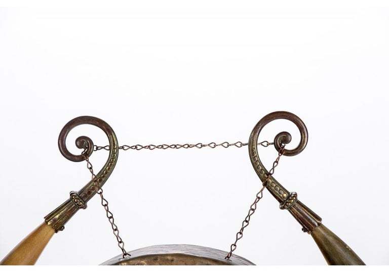 A fine older Asian gong with good traditional form. Double cow horns form the support for the hollow hammered brass gong. The horns are mounted with brass beaded scrolls on the tips for the chains supporting the gong. The horn bases with hoof- like