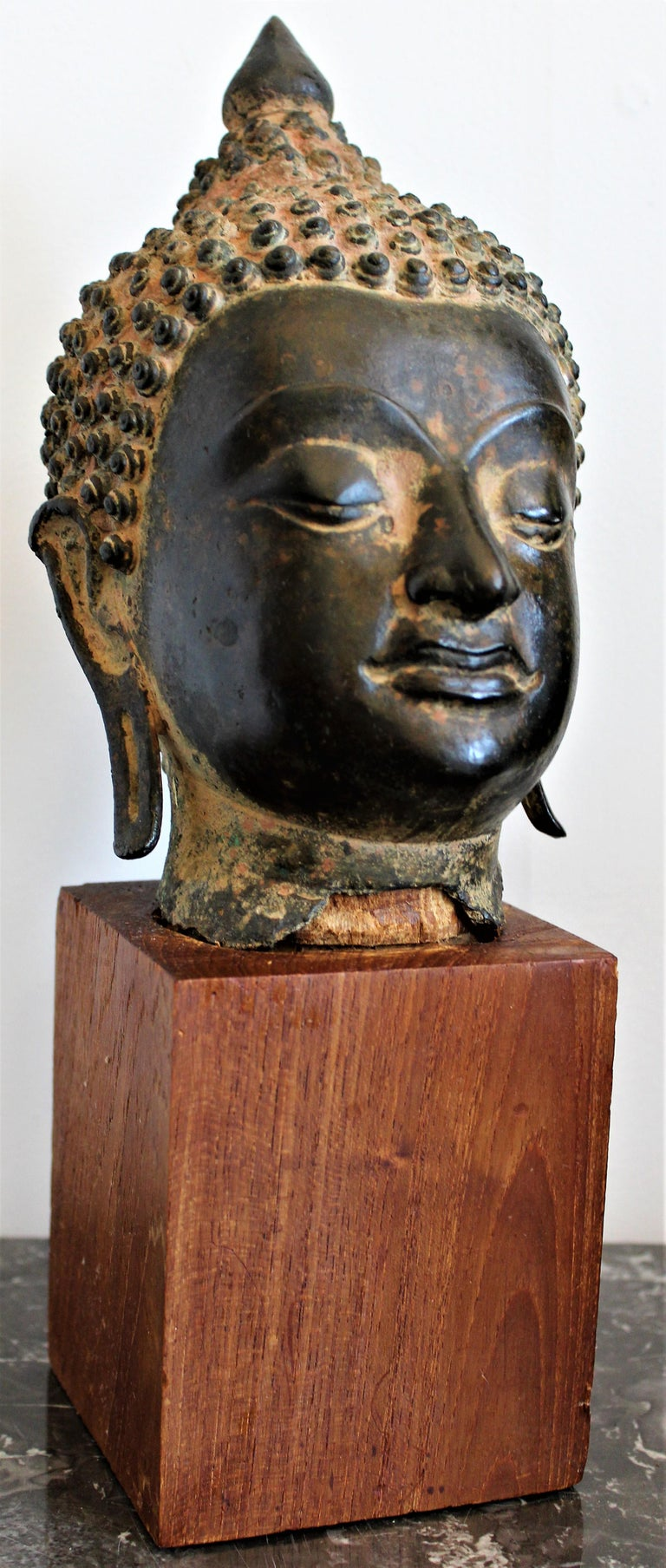 Antique Asian and extremely detailed cast bronze fragment of the head of Buddha, dating from the 18 century and presumably having Thai or Tibetan origins. The sculpture fragment is securely presented on a simple teak block.  The bronze head on its
