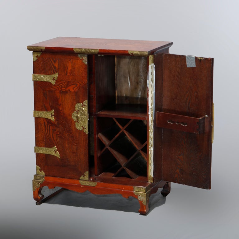 An antique Asian cellarette offers mixed wood construction with double compartment doors opening to interior segmented for bottle and other storage, brass strap hinges and hardware throughout as photographed, 20th century  Measures: 33.25