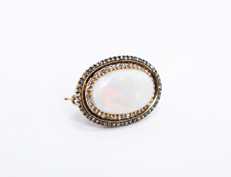 Beautiful handmade antique brooch set with an impressive Australian opal with an approximate weight of 35.00 carats measuring 20x30mm in a 43 claw setting. The opal is surrounded by two rows of rose cut diamonds, coronet set,  totalling to