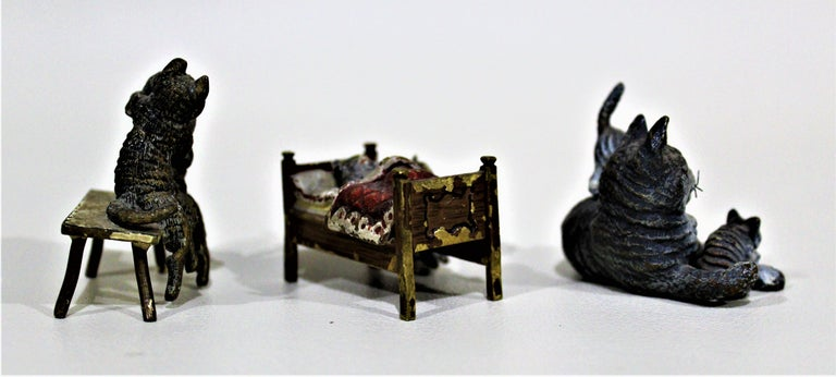 Lot of three ornately cast and cold-painted antique Austrian bronze miniatures of whimsical cats. These highly detailed sculptures date from circa 1900-1920.  Approximate dimensions of figurines: (L/W/H)  Cats on a bench: 2 x 1.20 x 2 Cats in