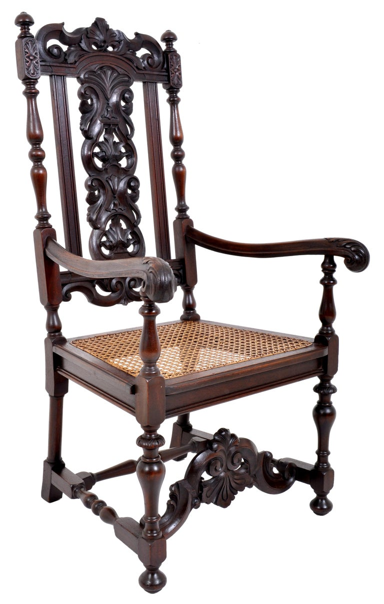 Antique Baroquecarved walnut throne chair, circa 1880. The chair having a carved crest with a shell motif to the center flanked by a pair of finials, the central black-splat heavily and deeply carved with acanthus leaves and flanked by turned