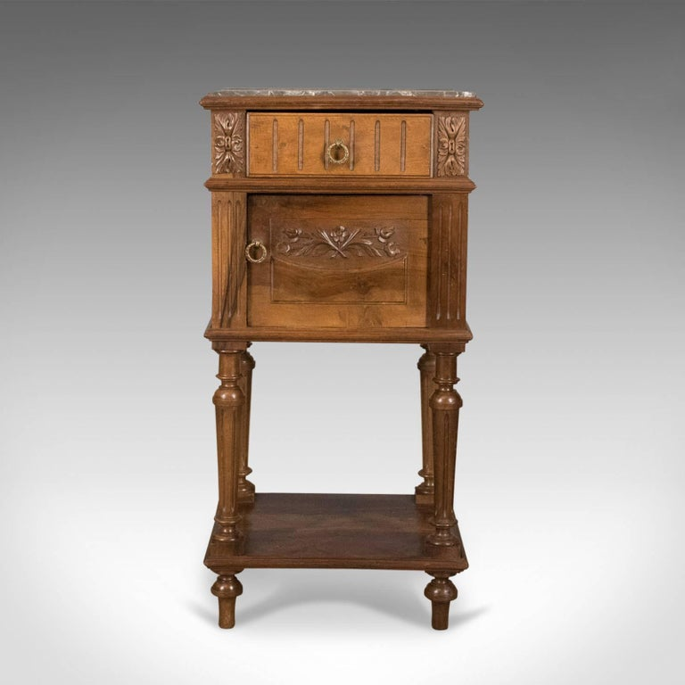 This is an antique bedside cabinet, an English, Victorian marble-top pot cupboard in walnut dating to the end of the 19th century, circa 1900.  Mellow biscuit tones to the well figured walnut Marble top in good order throughout Grain interest
