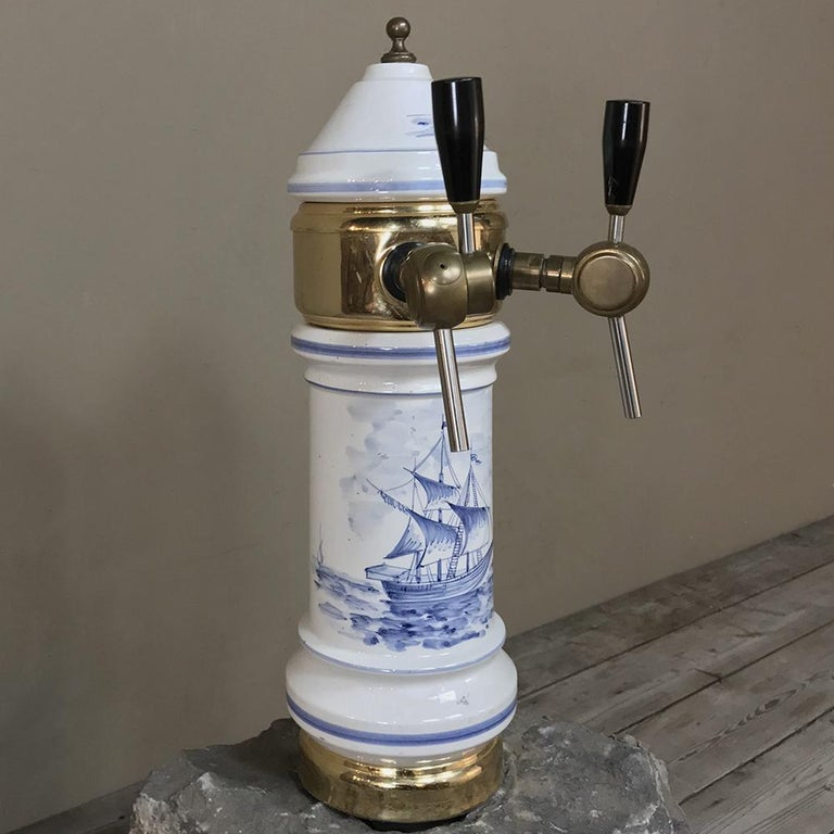 Antique Belgian beer tap is the perfect finishing touch to your home bar! Hand-painted with nautical scenes, it features a blue and white main body mounted with brass fittings and polished wood handles. What a great addition to your bar! circa