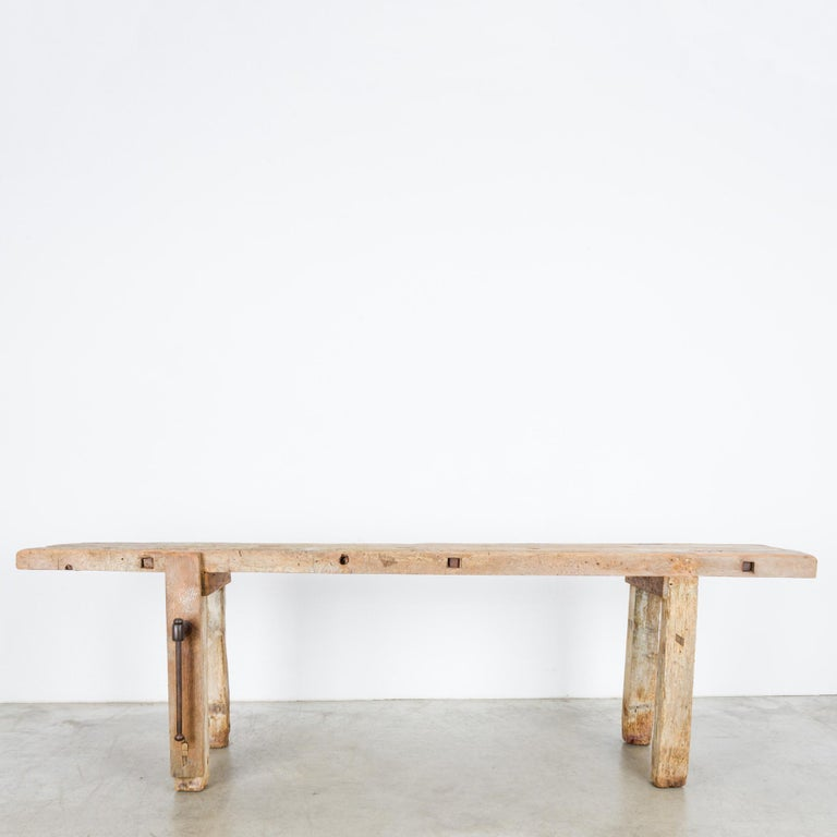 A wooden work bench from Belgium, circa 1900. A work surface formed of two long, narrow planks rests on a pair of a-frame legs, a classic carpenters bench, equipped with its original iron leg vice. The finish of the wood is raw and natural,