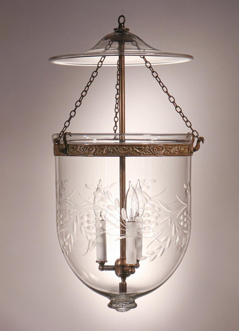 Antique bell jar lanterns of this quality and size are difficult to find. This especially lovely hand blown glass English pendant features a finely etched vine and berry motif and an original brass band with embossed floral design. The lantern has