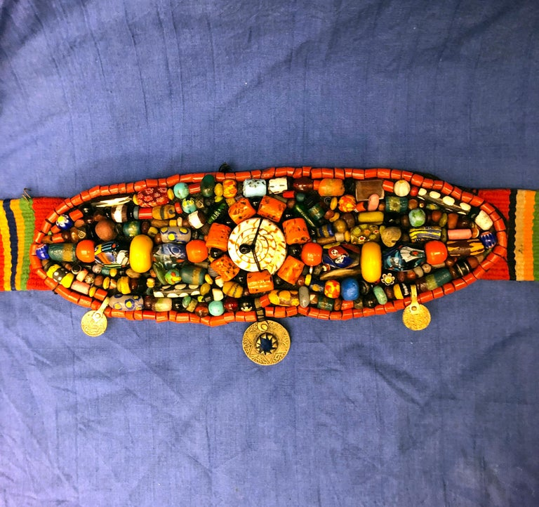 This beautiful antique belt is a fantastic example of traditional Moroccan Berber weaving and jewelry. A tightly woven striped wool design emanates from centerpiece of the belt, in vibrant naturally dyed green, orange, black, red, blue and yellow.