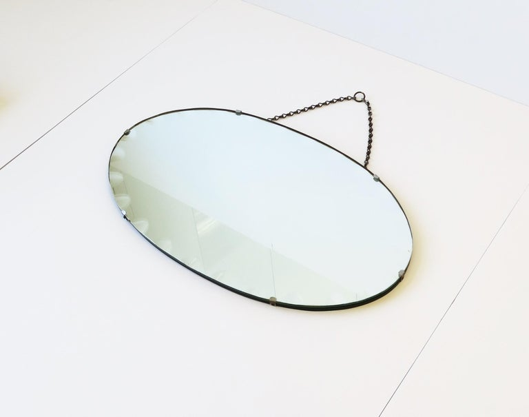 A very beautiful antique wall or vanity mirror with a modern bevel design around, circa early 20th century. Piece is oval in shape featuring this modern bevel; A design I haven't seen before. This bevel design can be seen best in images 3, 5, and 7.