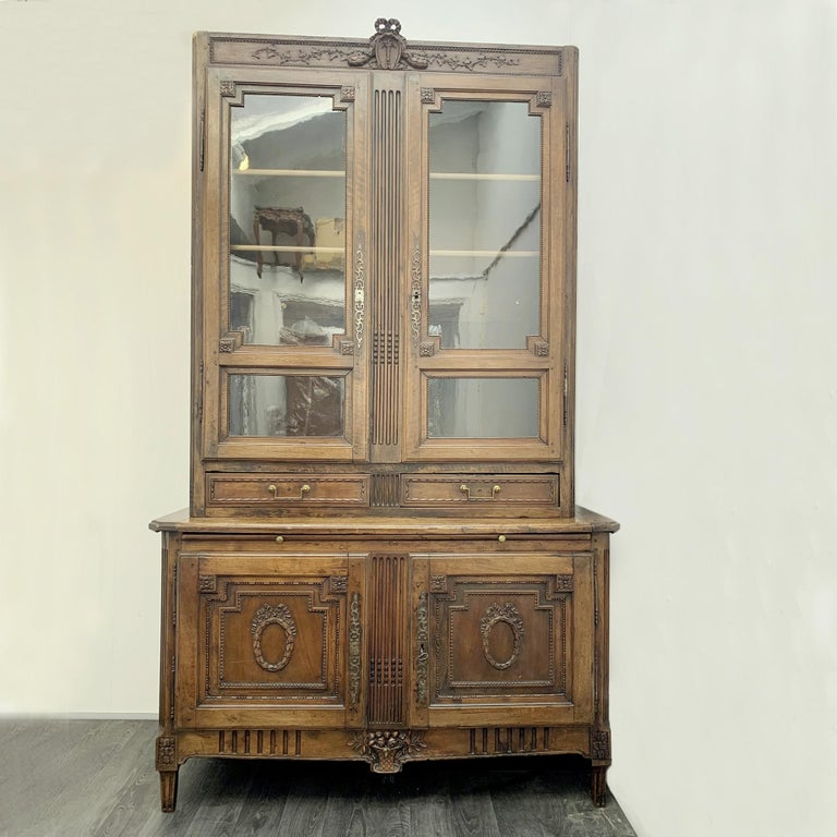 Bookcase and display cabinet in walnut with refined hand carvings by François Claude Menant (1757-1793) France, Louis XVI period (and Restoration). Menant was accepted as a member of the guild of master craftsmen, circa 1780. This elegant French