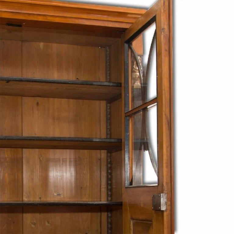 A bookcase from the Biedermeier period, made in the 1830s and featuring a walnut veneer and decorative motifs typical for this period. This bookcase has been professionally refurbished using shellac polish and remains fully functional.
