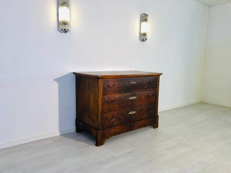 Original antique Biedermeier commode from a German castle, build in the 1850s. It convinces with its classic design, the dark brown walnut veneer and original key plates and handles made of brass. The item is currently under restoration and will be