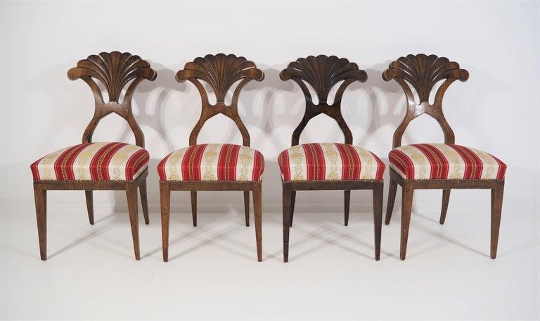 4 Biedermeier dining chairs. On elegant legs, shell-shaped backrests with walnut veneer. Established in the 19th century. Material: walnut. Dimensions: (H x W x D) 92 x 45 x 55 cm.