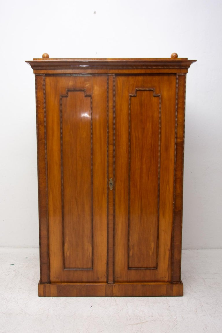 A shelf cabinet/ storage cabinet from the Biedermeier period, made in the 1830s and featuring a walnut veneer and decorative motifs typical for this period. This cabinet was professionally refurbished using shellac polish and remains fully