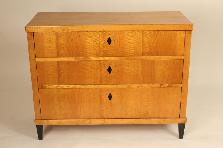 Antique Biedermeier style three-drawer birch chest of drawers with ebonized feet and escutcheons, late 19th century. With restorations.