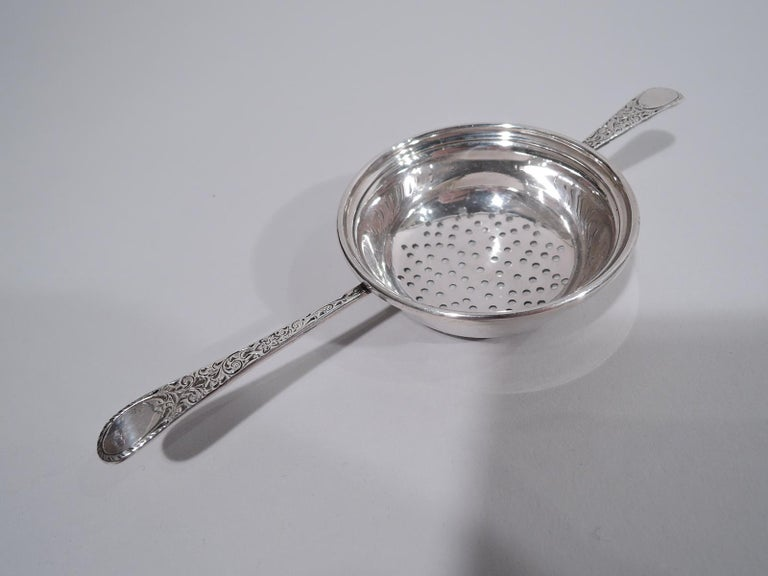 Edwardian sterling silver tea strainer. Made by Birks in Canada, ca 1920. Round bowl with pierced-star bottom. Tapering handle mounted to one side; shorter same mounted to other. Supports have pretty scrollwork and oval terminals (vacant). Majorly