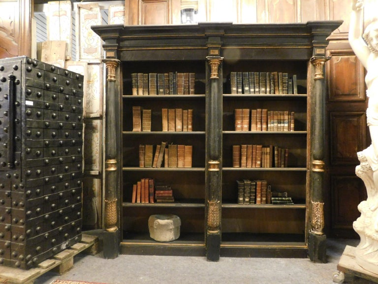 Ancient solid wood bookcase, hand lacquered in black and gold, with columns carved with acanthus leaves and open shelves, built at the beginning of the 19th century, from a palace in northern Italy. made in the first half of the nineteenth century,