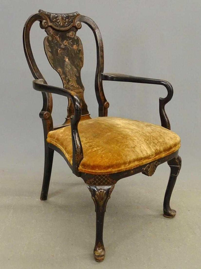 The antique black Japanned armchair in the Queen Anne style with upholstered seat is decorated with a Oriental figure crossing a bridge with a flowering branch overhead. The knees of the cabriole legs are embellished with stylized shells as is the