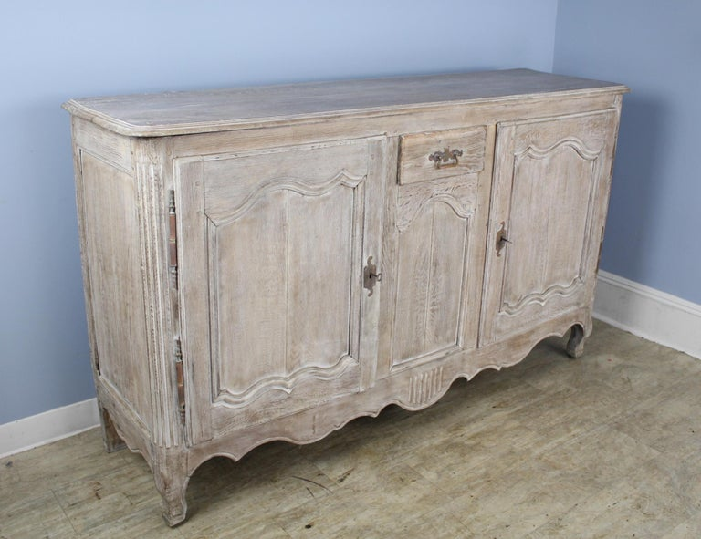 Wonderful Classic French oak buffet made modern with bleaching. The doors are well paneled as are the sides. There is a simply shaped apron. Feet are well-shaped also. Small center drawer for extra storage, and the reeded vertical quarter columns at