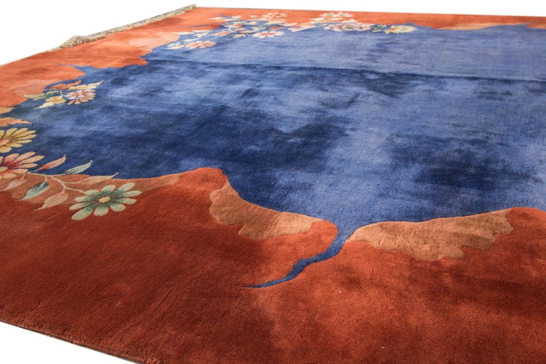 Beautiful antique Chinese Peking hand knotted wool rug with a blue field, orange frame, and multi-color accents in an all-over Classic Chinese floral design.  This rug measure: 9' x 11' 5