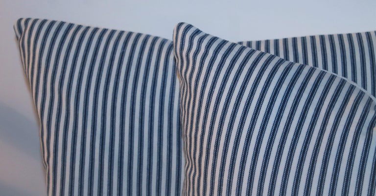 Antique ticking pillows with white linen backings. The inserts are down & feather fill. The collection of four pillows, two pairs.