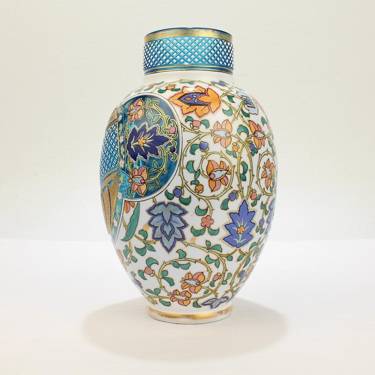 A very fine Bohemian aesthetic period enameled and cut-to-clear art glass vase.  In two colors with a white cased top layer cut to reveal a blue ground in the style of the Moser or Josephinenhütte factories.  With diamond cuts, enamel stylized
