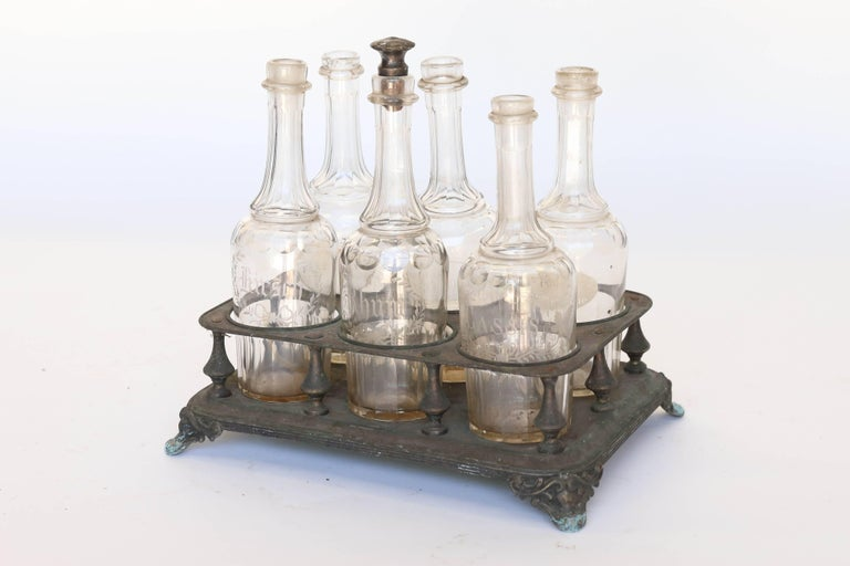 Found in France, a very old and lovely bottle holder with six etched bottles. Made of tin, the holder stands on four ornate feet and holds three liquor bottles elaborately etched 'Kirsch', 'Rhom', and 'Cassis'; the three remaining bottles are less
