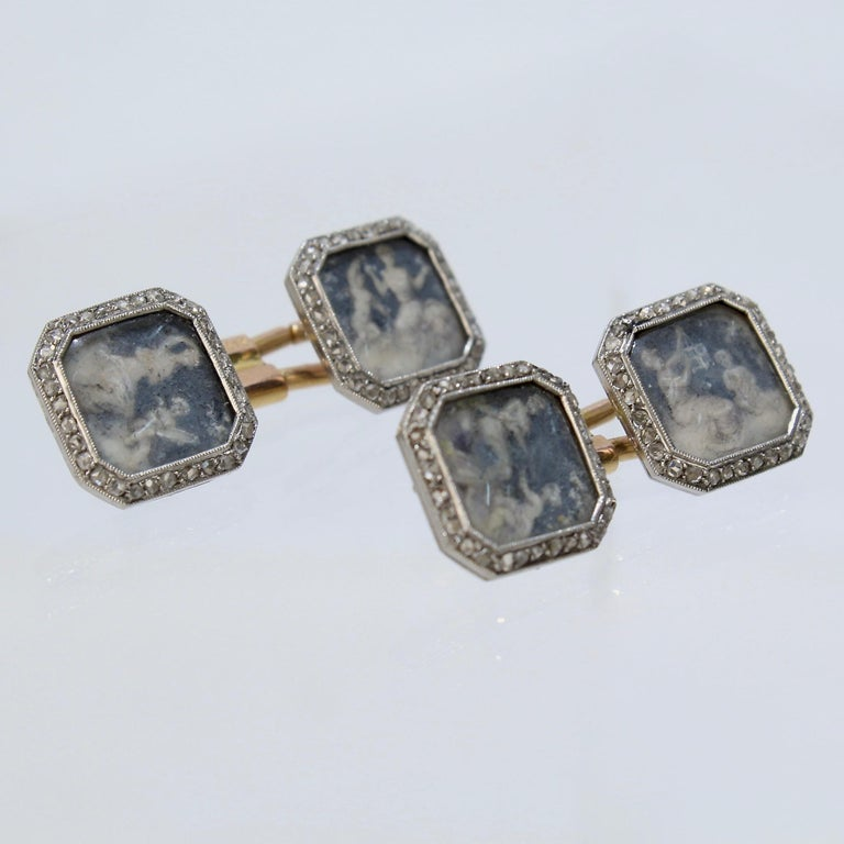 An extraordinarily rare pair of antique Boucheron cufflinks.  With diamond-set platinum frames encasing hand-painted classical scenes of a woman and a cherub under glass bezels. The scenes are possibly allegories of the Arts.  30 small diamonds
