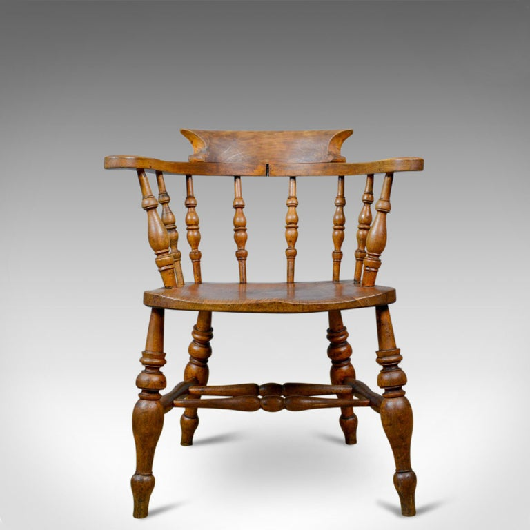 This is an antique bow-back elbow chair. An English, Victorian, elm, 'smokers', or 'captains', chair dating to circa 1890.  An appealing country kitchen, bow back armchair Grain interest in a wax polished finish Solid and stable offering a
