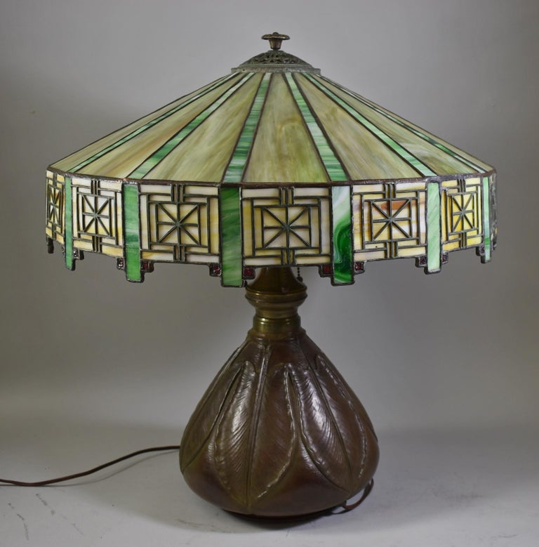 Antique Bradley & Hubbard Arts & Crafts leaded glass table lamp with Bryant sockets and original pulls. Adjustable height. Artichoke leaf pattern on the base. Great patina. Signed on base at socket cluster. 20