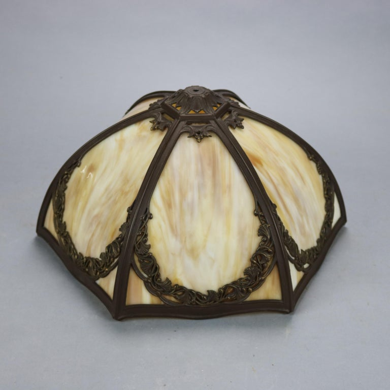 An antique Arts & Crafts table lamp by Bradley and Hubbard offers cast floral shade housing bent slag glass panels over double socket base, maker signed, c1920   Measures: 21.25