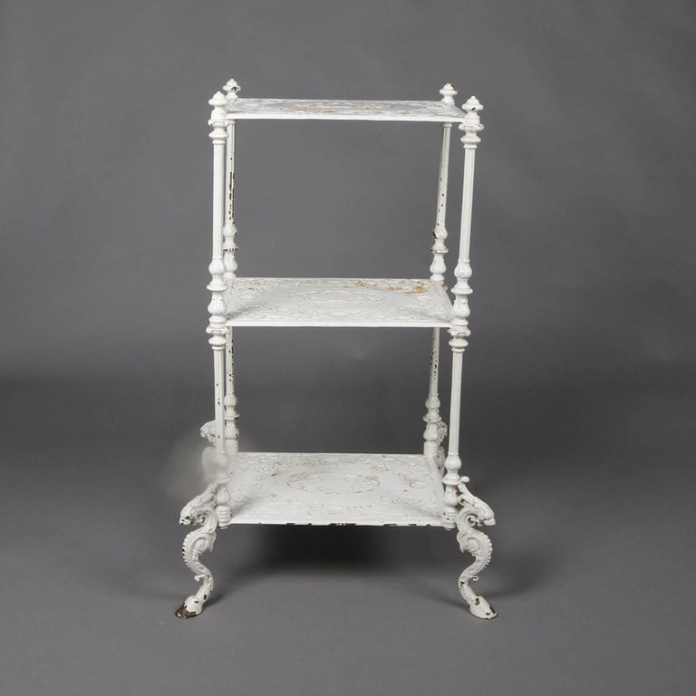 Antique Bradley & Hubbard School figural cast iron plant stand features cast iron construction with three tiers having low relief foliate decoration and cornered by shaped column legs with finial heads and s-scroll dragon form legs having hoof feet,