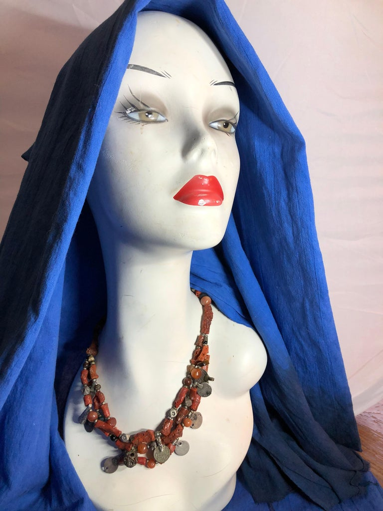 This museum-quality antique coral necklace is a true find. Large pieces of true red branch coral are interspersed with antique coins and etched and stamped silver beads. Other beads include tiger's eye, desert stone, amber and more. Three strands