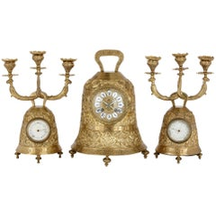 Antique brass clock set with religious decoration