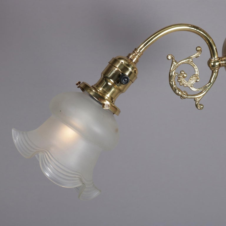 Antique gas conversion hanging light fixture features brass frame with three scroll and foliate form arms terminating in tulip form frosted glass shades, circa 1910.  Measures: 37