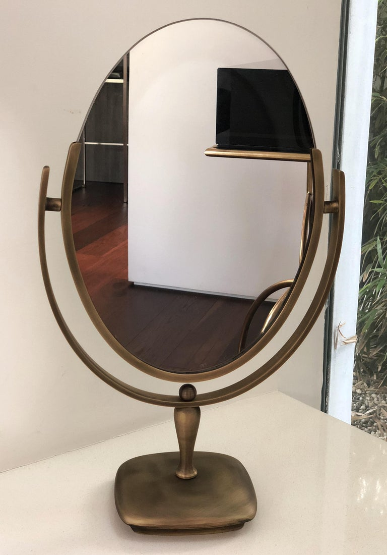 Beautiful oval mirror designed and manufactured by Charles Hollis Jones in the 1960s. The mirror has an antique brass finished frame and base, the mirror is double sided and it can be flipped to be used on either side.  Measurements: 20