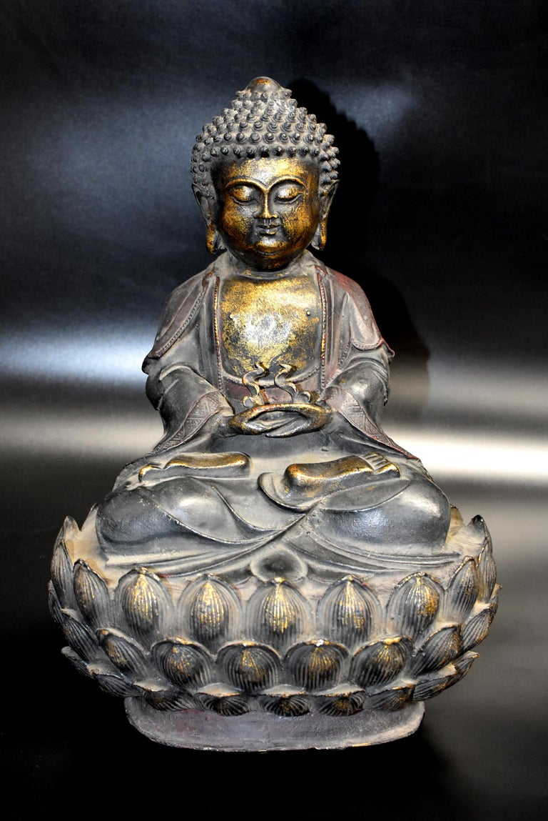 A large, beautiful bronze Buddha. Flanked by pendulous earlobes, the full face with slender bow-shaped eyes and hooded eyelids casting a serene and meditative aura with downcast look, below evenly arched eyebrows tapering at the ends issuing from