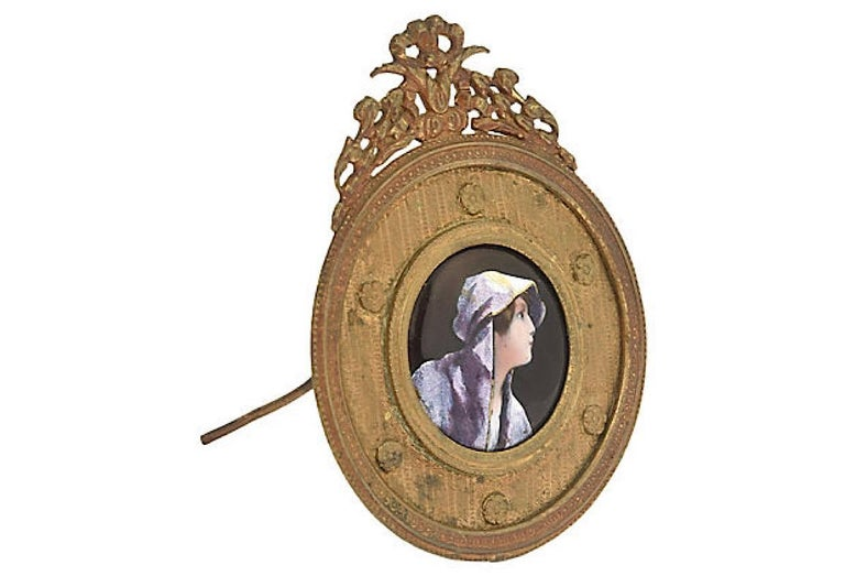 Enamel painting of a woman's profile on copper set in an ornate bronze frame. The back has an easel as well a ring so it can be set on a table or mounted on the wall. Age wear, tarnished, light scratches.