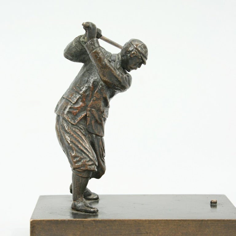 Bronze golfing figure. A good golf figure made of bronze in full backswing position. The golfer is dressed in period clothing, plus fours, jacket and cap and is on a rectangular base inscribed 'PLUS'.