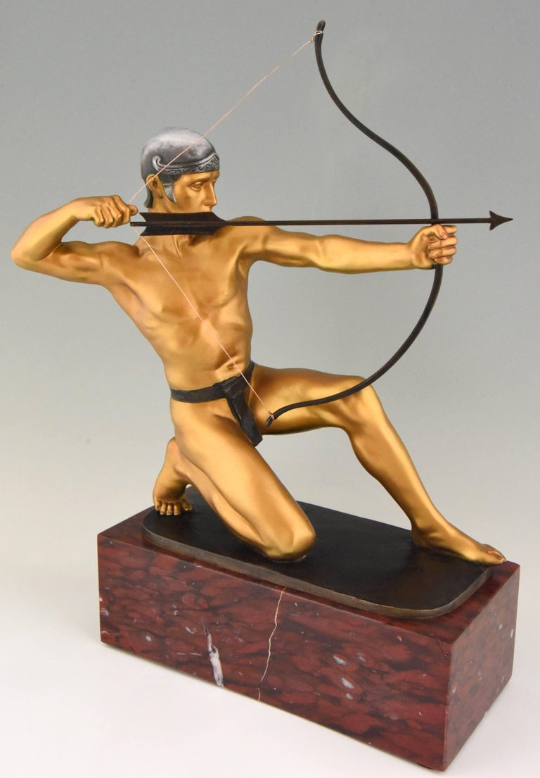 Antique bronze sculpture of an Archer with bow by the German sculptor Rudolf Kaesbach. The male nude is aiming in a kneeled pose and is wearing a silver helmet.  The bronze has a multi-color patina and is mounted on a Belgian red marble base.