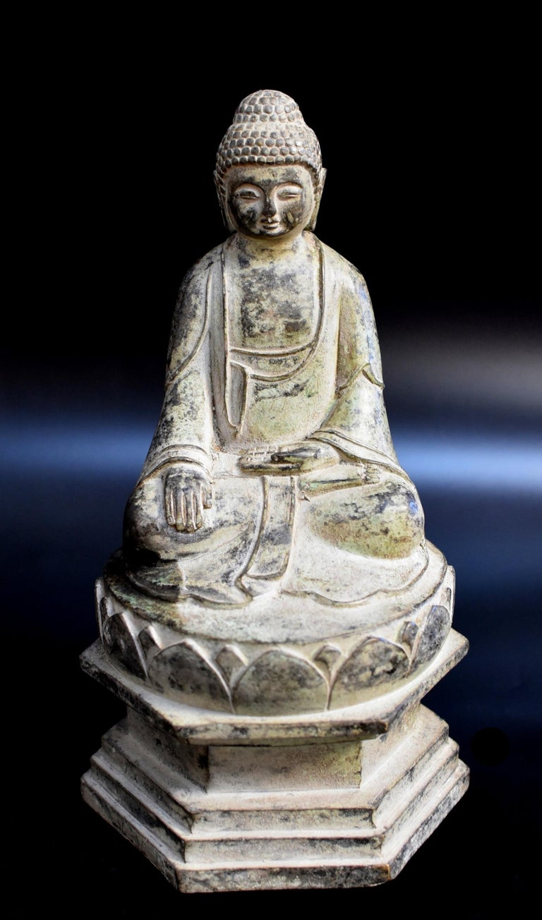 A beautiful bronze statue of Young Buddha. Seated in dhyanasana on lotus throne elevated on a high pagoda base, the right hand in bhumisparsha mudra and the left in dhyana mudra, wearing a flowing robe draping over the shoulders and pooling