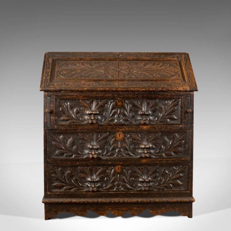 This is an antique bureau in English oak. A Victorian green man writing desk dating to circa 1880.